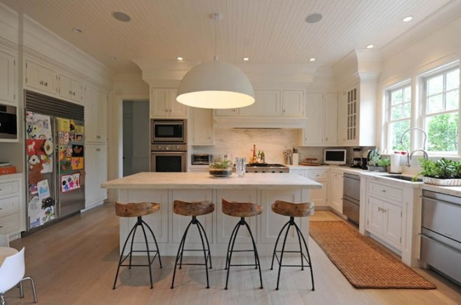 Oversized meets rusitc!  These rustic wood stools create an beautiful contrast against this white kitchen.  An oversized white dome pendant casts a beautiful warm glow to this eat-in island.